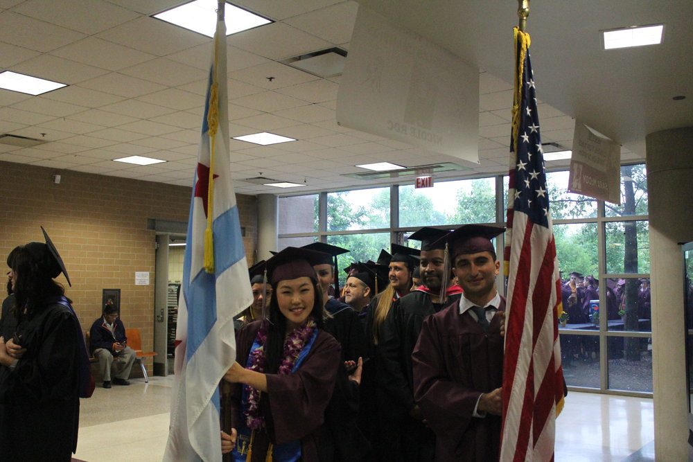 Abigail Kim and Jadd Oweimrin, Adv. 803, lead their fellow classmates into the gymnasium, holding the US and Chicago flags