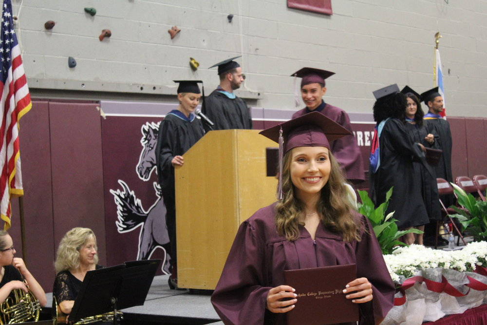 After walking across the stage, Viktoria Kontseva, Adv. 800, shows off her new diploma