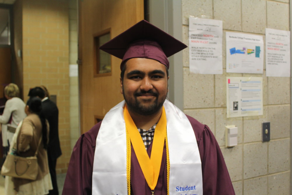 Valedictorian Ibraheem Khan stands in the cafeteria among family and friends, all of whom are proud of the speech he gave