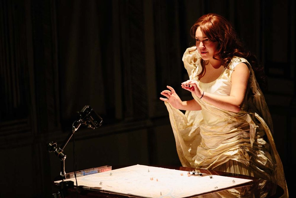 An opera singer, manipulating the map of Paris, symbolizes the French aristocracy.