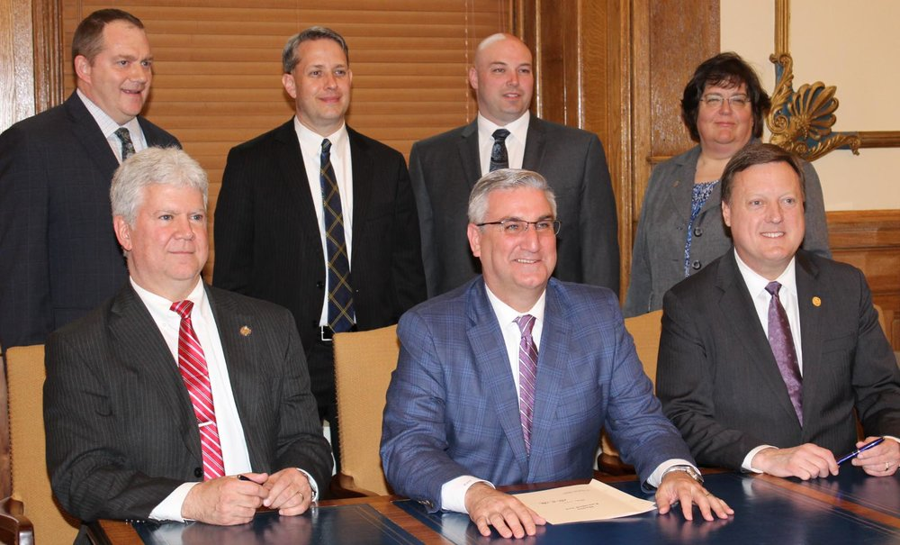 Indiana prosecuting attorneys from Hancock, Washington and Hendricks County participated in Governor Eric Holcomb's signing of HB 1033 on April 23. The bill holds habitual offenders fully accountable for their out of state criminal history. Front row, from left, are, bill author Rep. Thomas Washburne, Gov. Holcomb, and Senate sponsor Sen. Eric Koch. Back row, from left, are: Indiana Prosecuting Attorneys Council Assistant Executive Director Chris Naylor, Hancock County Prosecutor Brent Eaton, Washington County Prosecutor Dustin Houchin and Hendricks County Prosecutor Patricia Baldwin. (Photo courtesy of Indiana Prosecuting Attorneys Council)