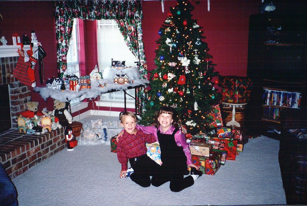 I know your eye immediately goes to the purple shiny shirt, the velvet overalls, and the black shoes with white socks, but if you look to the right of the tree, you will see the table with presents on top of it. Also, check out that sick VHS collection.