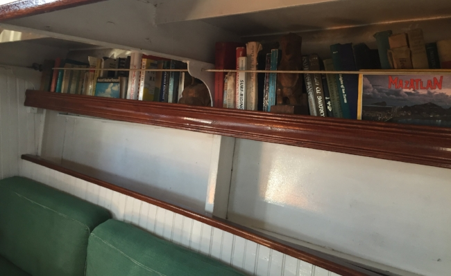 the ruby travels with souvenirs of past trips and books filled with sailing yarns.