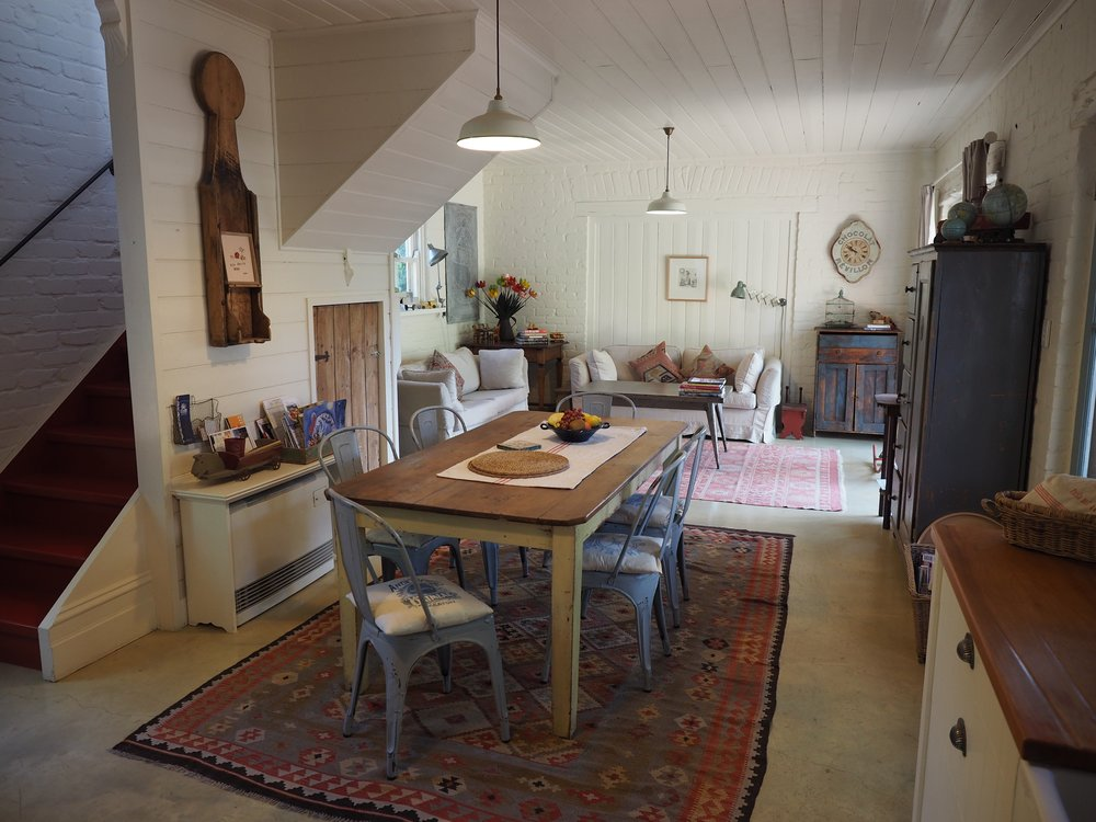 A farmhouse table, industrial chairs, Turkish rugs and rustic timber cupboards all come together in perfect harmony.
