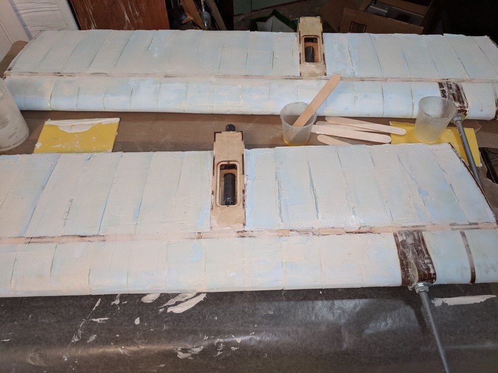 Wing frames and cores assembled, sanded, and ready for glass. Note the counterweight boom in the lower left.