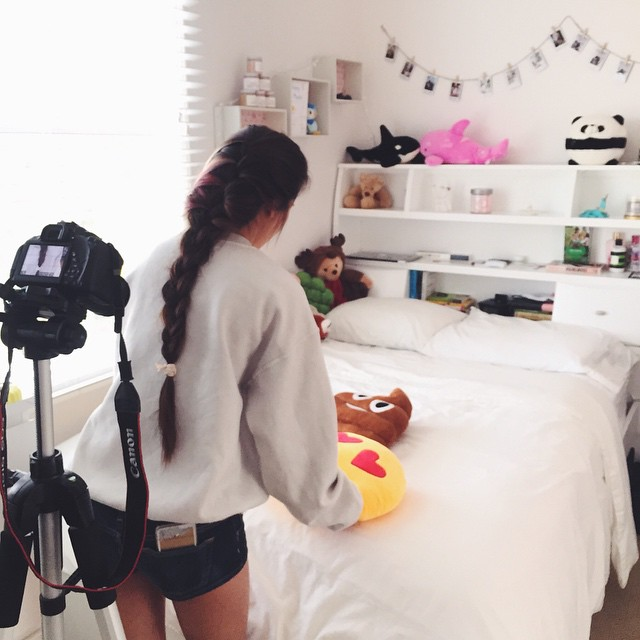 Joyce setting up a photo shot for emojipillow in her room.