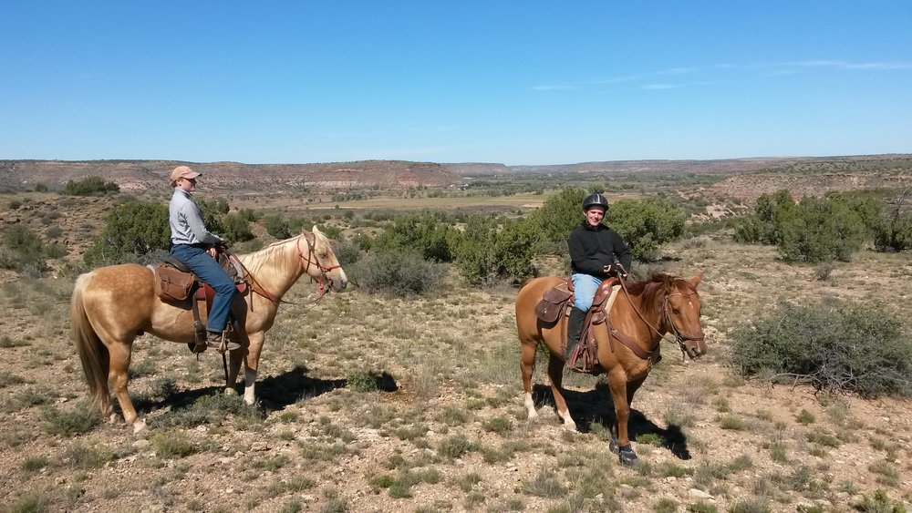 A trail ride in nice weather (left to right: Melanie on Johnny and Leo on Whiskey) with the Pecos Valley in the background.  Ein Trailritt in herrlichem Wetter (links nach rechts: Melanie auf Johnny und Leo auf Whiskey) mit dem Pecos Valley im Hintergrund.