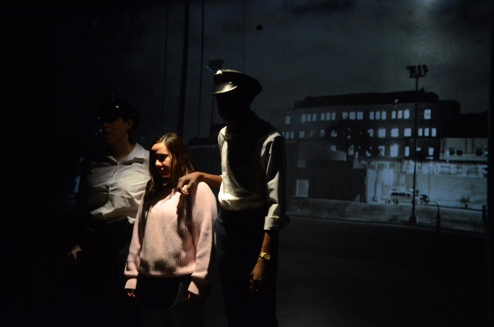 Elizabeth Mason as Good Apple, Alaithia Velez as Jailbird, and Brandon Pegram as Officer Jordan at Trinity Street Players.