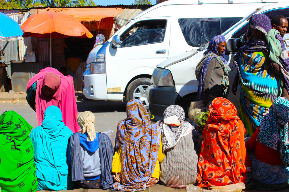 Locals in Harar sit and wait as buses go by