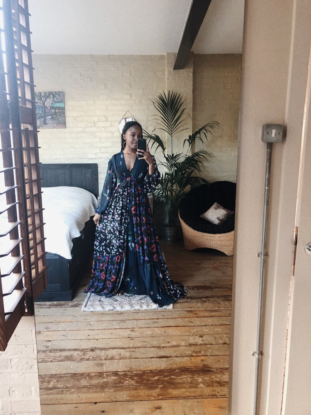 A woman wearing a floral maxi dress, surrounded by plants in a London apartment.