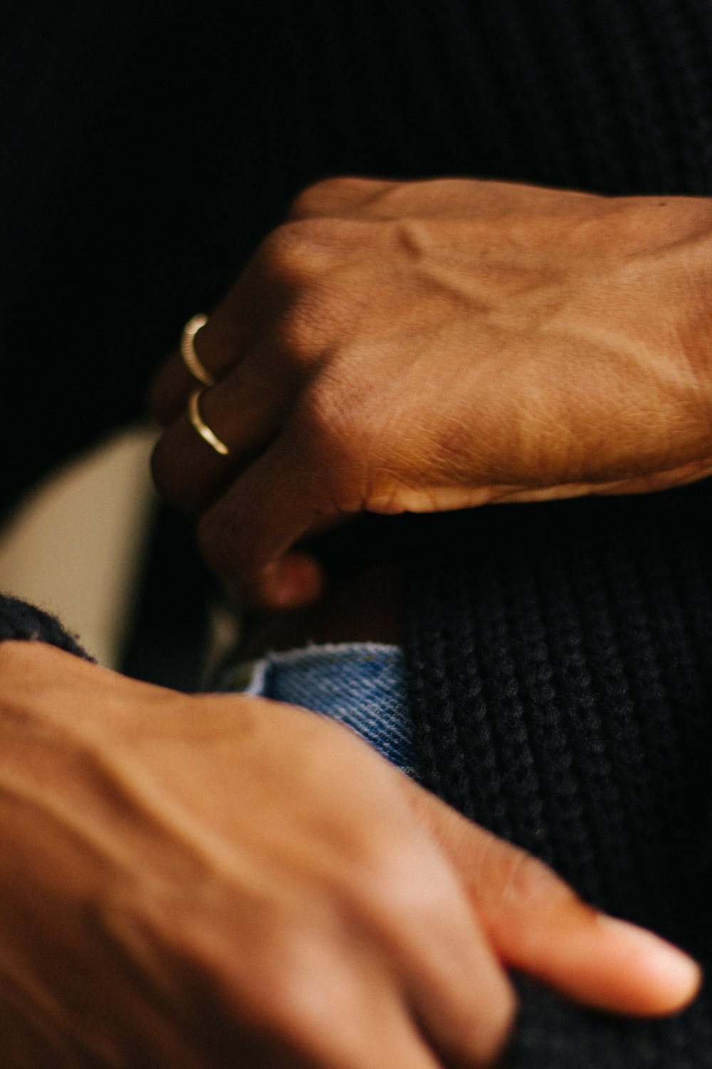 A close up photograph of gold rings and levi jeans.