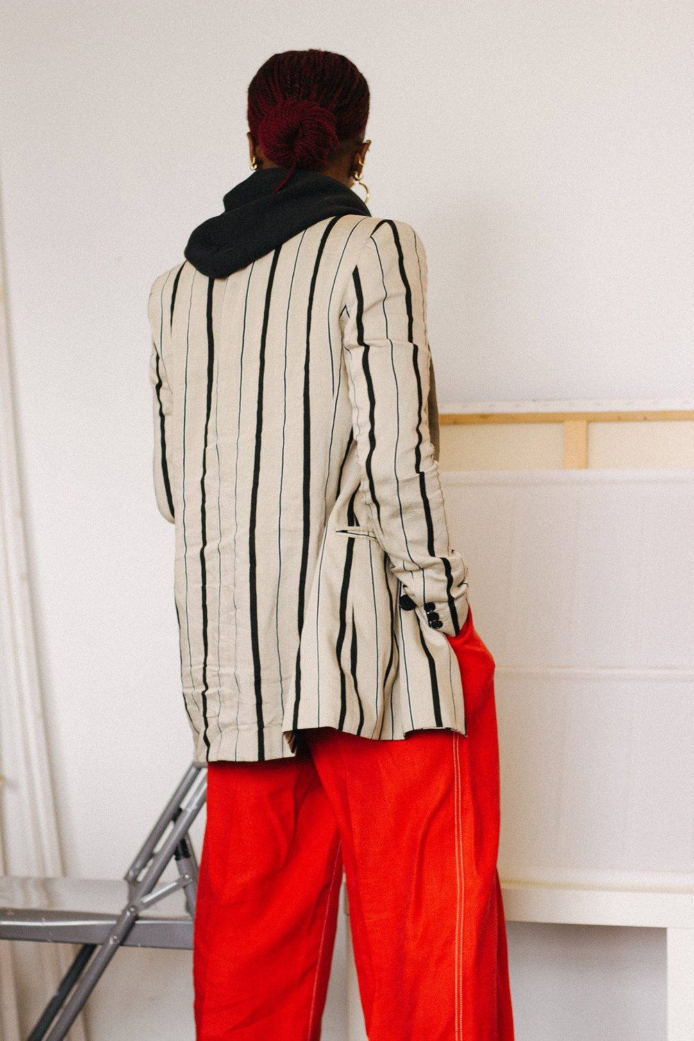 A fashionable woman wearing red trousers, a striped blazer, and a leather bag.