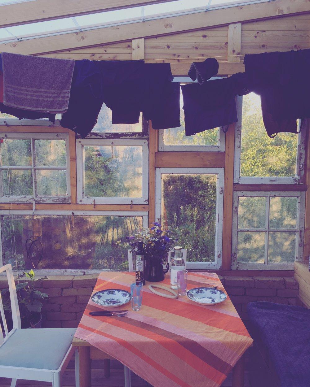 Om kvelden er det så vakkert lys gjennom de støvete gamle vinduene. Vi har også stablet et lag ubrente leirstein opp som termisk masse, så holder solvarmen litt utover kvelden. Godt for oss og godt for tomat- og agurkplantene våre.