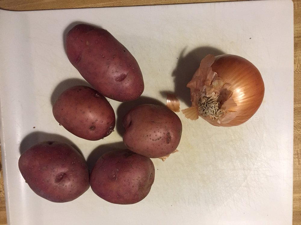 Organic red potatoes and a yellow onion