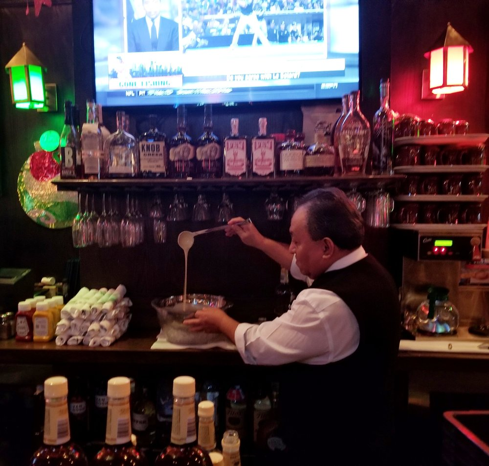 A MIller's Pub bartender showing off the batter that goes into a Tom and Jerry