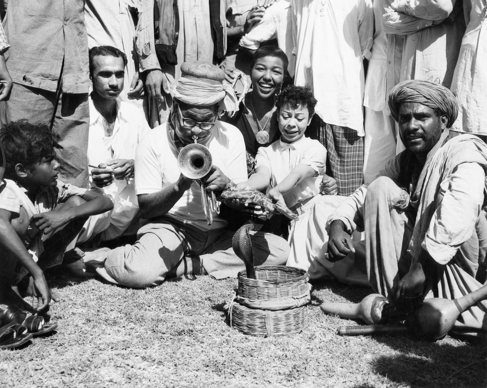Dizzy Gillespie (with turmpet), singer Dottie Salter (holding the snake) and trombone player Melba Liston (at back), charm a cobra in Karachi, Pakistan, 1956. Credit: Malcolm Poindexter III / Courtesy of the Institute of Jazz Studies, Rutgers University