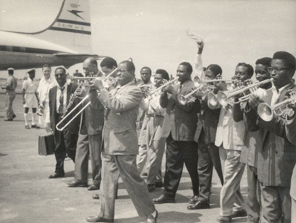 Louis Armstrong (center) is greeted by nine local trumpet players at the airport in Accra, The Gold Coast (present day Ghana) in 1956. Credit: Courtesy of the Louis Armstrong House Museum