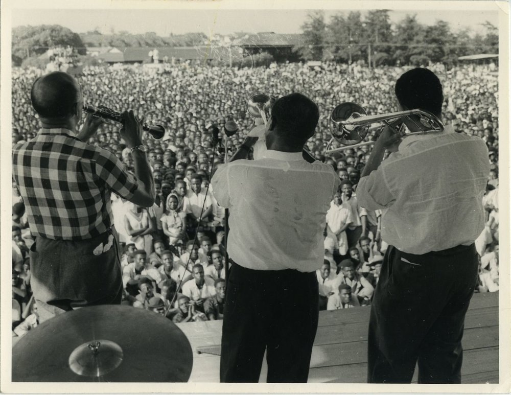 Louis Armstrong (center) plays in Accra, The Gold Coast (present day Ghana) in 1956 to a crowd estimated at 100,000. He's flanked by clarinetist Edmond Hall (left) and trombonist Trummy Young (right). Credit: Courtesy of the Louis Armstrong House Museum