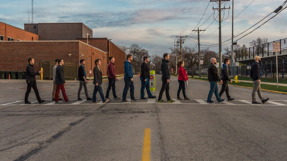 Members of the Heisenberg Uncertainty Players walking across a street (like Abbey Road)