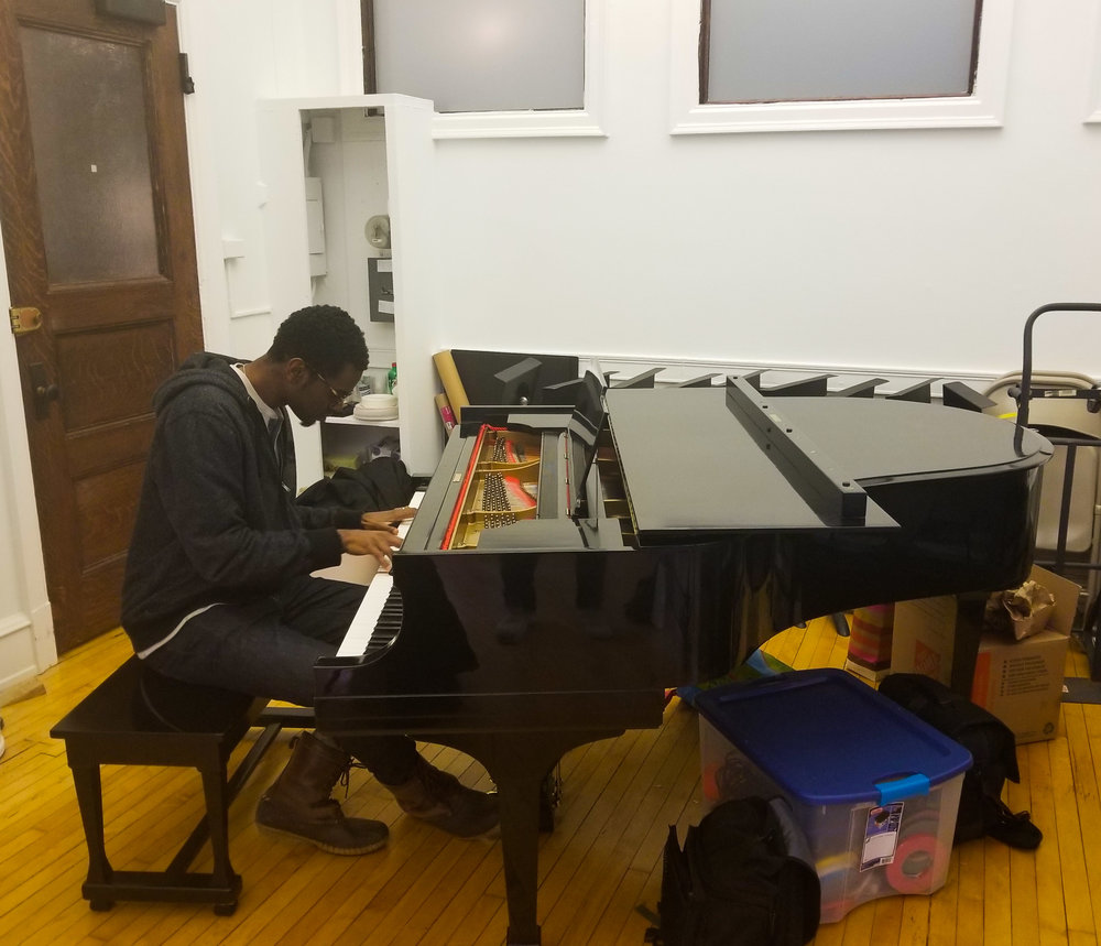 Julian Reid playing piano on the 9th floor of the Fine Arts Building