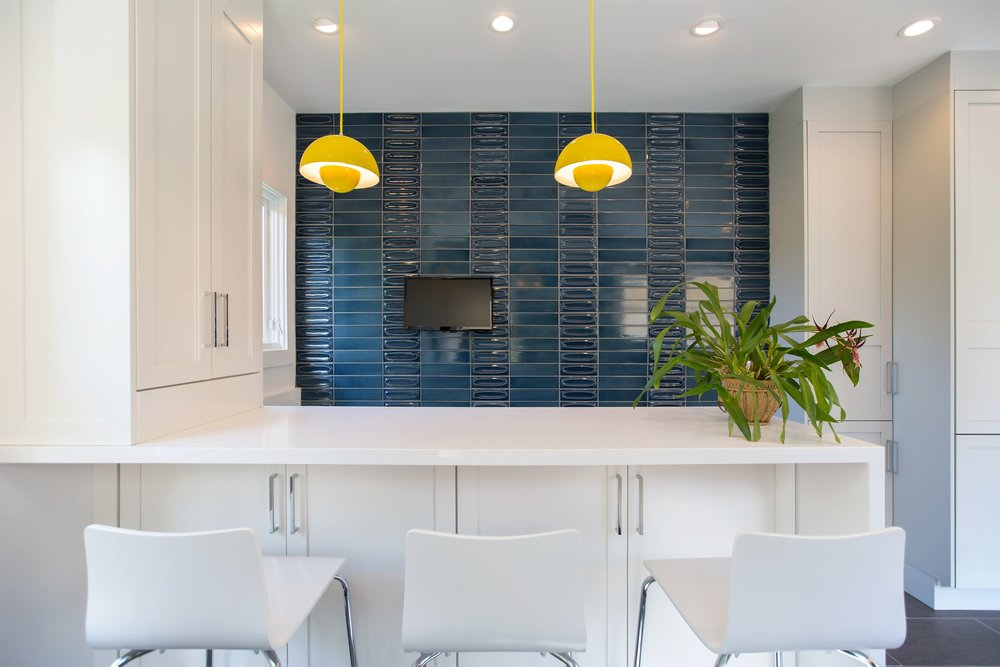 william-adams-design-christmas-tree-lane-2-kitchen-white-bar-seating-blue-tile-wall-yellow-lights.jpg
