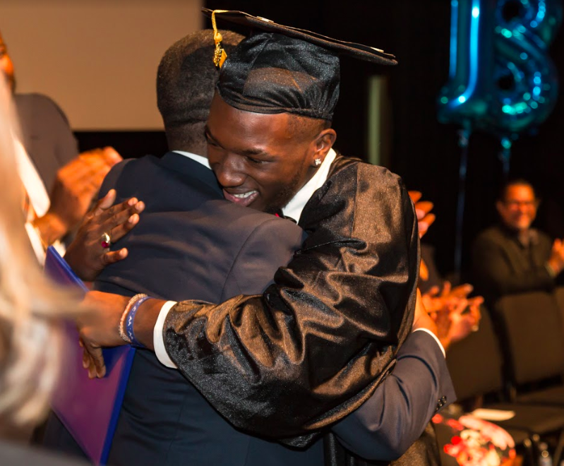 (Deuntae embracing Mr. Philemy, Principal, at the High School graduation ceremony)