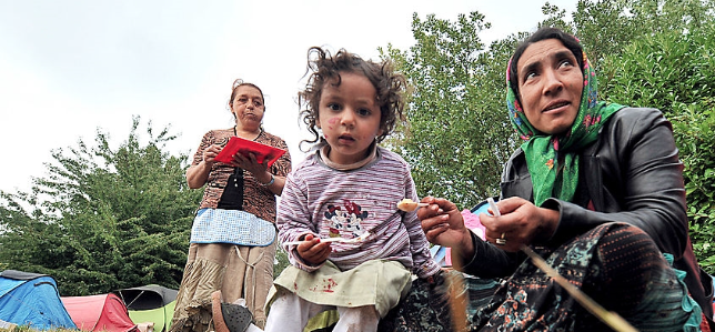 Romani people receiving food from volunteers after being displaced from another camp (image source: Getty Images)