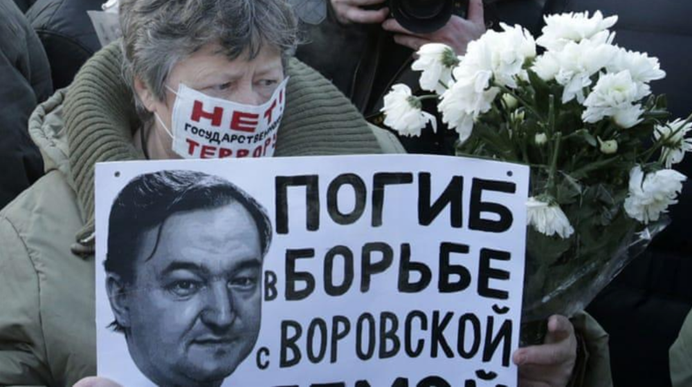 A woman holds a poster with a portrait of Sergei Magnitsky during a 2012 rally (Tatyana Makeyeva/Reuters)