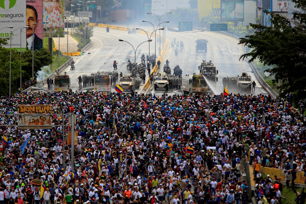 Photo:  Demonstrators clash with riot security forces while rallying against Venezuela's President Nicolas Maduro in May  Photo Courtesy: Reuters