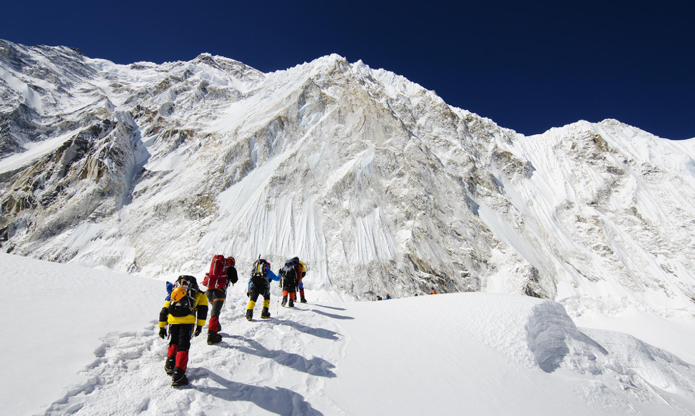 (climbers trek heads for the summit, Source:  https://adventure.howstuffworks.com/outdoor-activities/climbing/mt-everest-tourism.htm )