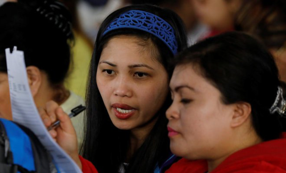 (Source: Reuters. Filipino workers fill out paperwork in Ninoy Aquino International Airport in Metro Manila, Philippines)