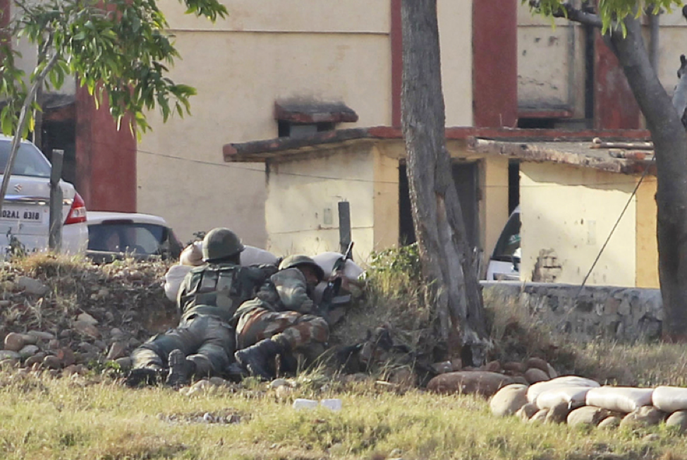 (Indian soldiers take cover as they wait outside of the compound militants are expected to be hiding in; Credit: Seattle Times, February 11th, 2018.  https://www.seattletimes.com/nation-world/6-dead-in-militant-attack-on-indian-army-base-in-kashmir/ ).