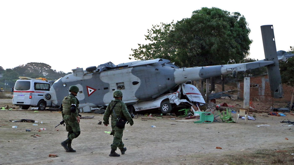 Description: Two military personnel investigate the crash site. Source:  AFP/ Getty Images/ LA Times