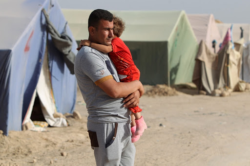 AHMAD AL-RUBAYE/AFP/Getty Images | Man and child in internally displaced persons (IDP) camp in Iraq