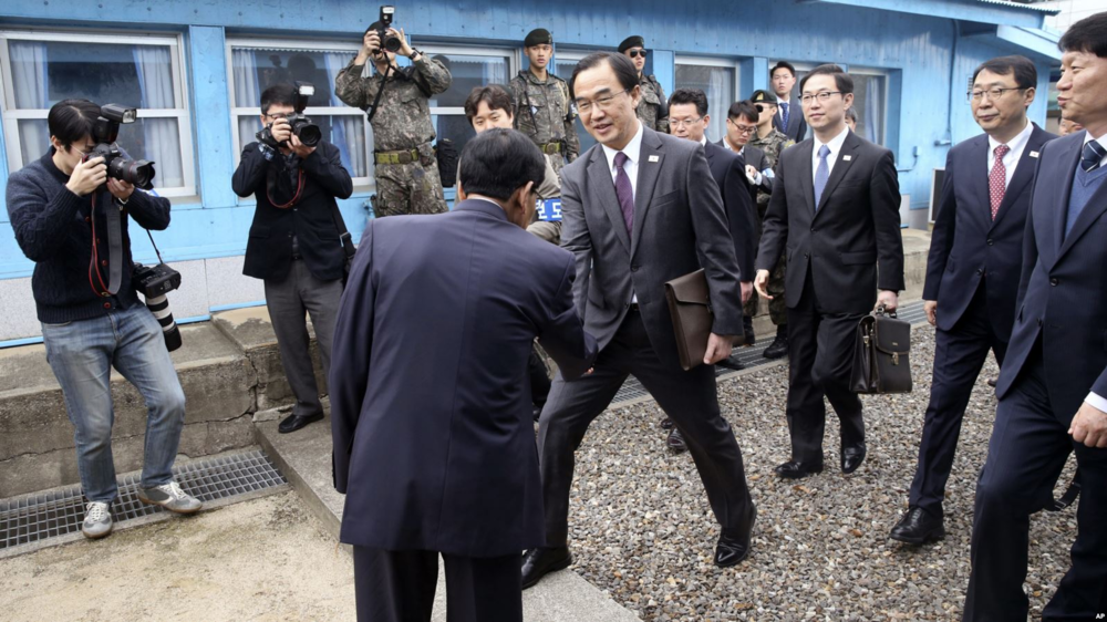 [South Korea's Unification Minister Cho Myoung-gyon (center) shakes hands with a North Korean official as he crosses the Korean border for a meeting on the northern side of the Joint Security Area at Panmunjom on Mar. 29, 2018. Photo: Korea Pool via AP]