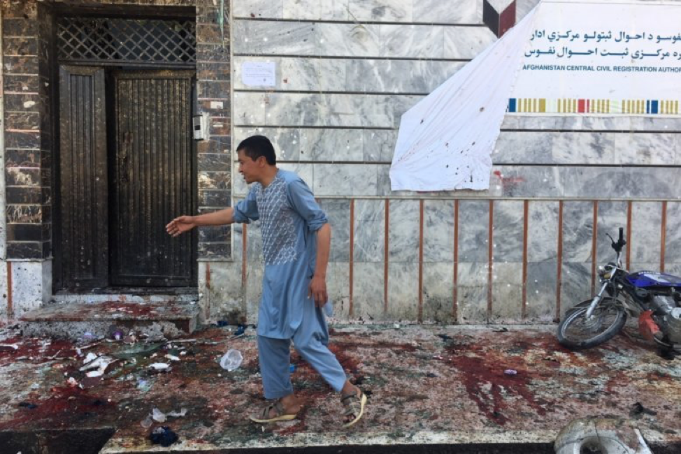 ( A man stands in front of the wreckage of the voter registration center bombed on Sunday ; Credit: WTOP, April 22nd, 2018).