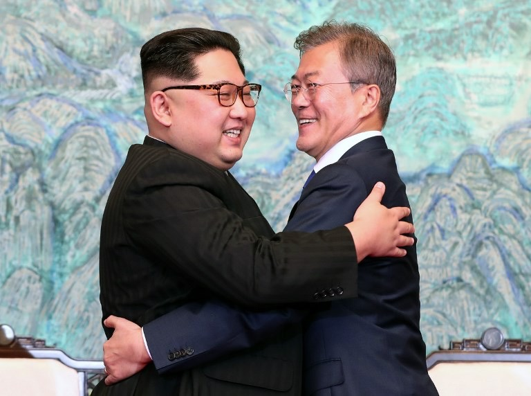 (North Korea's leader Kim Jong-un and South Korean leader Moon Jae-in hug each other during Friday's summit. Source:  AFP )