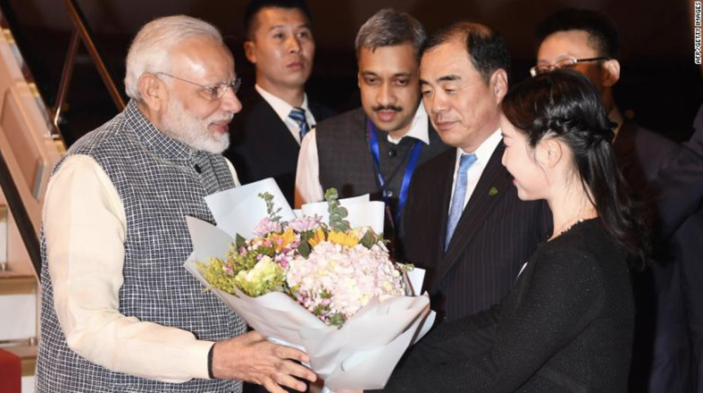 Indian Prime Minister Narendra Modi, left, receives a bunch of flowers after arriving in Wuhan in China's central Hubei province on April 27, 2018. Source: CNN