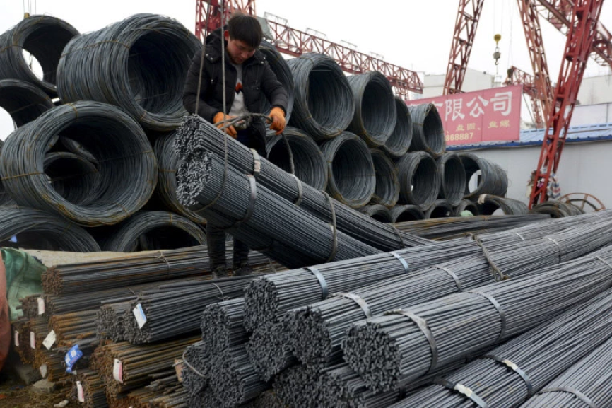 A worker loads steel products onto a vehicle at a steel market in Fuyang in central China's Anhui province. AP Photo.