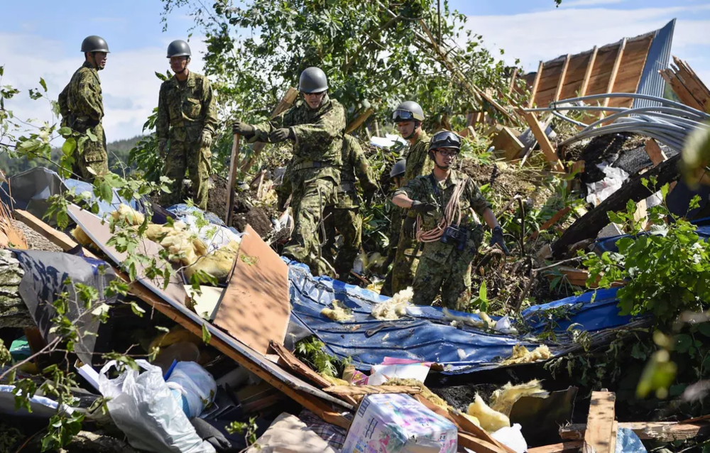 [Photo: Members of the Japan Self-Defense Forces (JSDF) search for survivors in hard-hit Atsuma, Iburi Subprefecture, Hokkaido Prefecture, in the wake of the earthquake. Photo:  Kyodo/Reuters ]