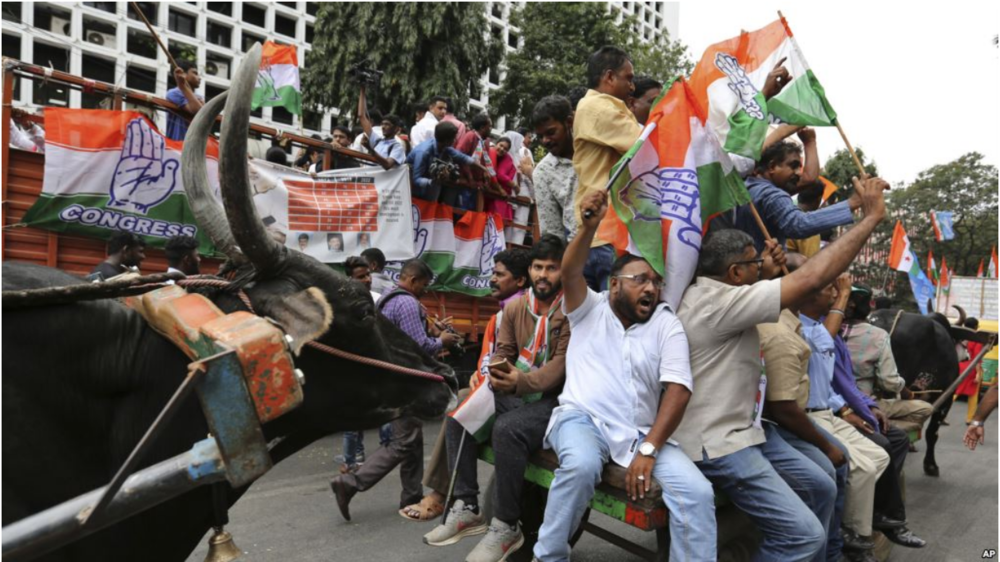 ( Members of the Congress opposition party encourage protesters in Bangalore, India ).