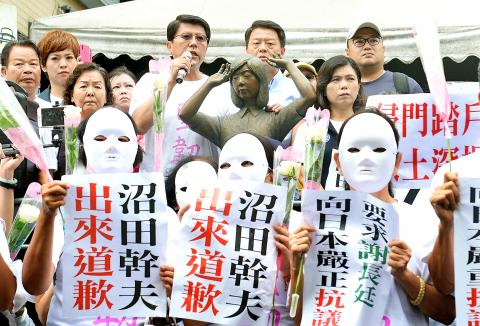 Tainan City Councilor Hsieh Lung-chieh (holding microphone on right), holds a news conference by the bronze statue commemorating comfort women on Sept. 10 as demonstrators hold signs demanding Japan's representative to Taiwan Mikio Numata apologize for the incident and Taiwan's representative to Japan Frank Hsieh lodge a formal protest with Tokyo. Credit:  Lin Cheng-kung, Taipei Times