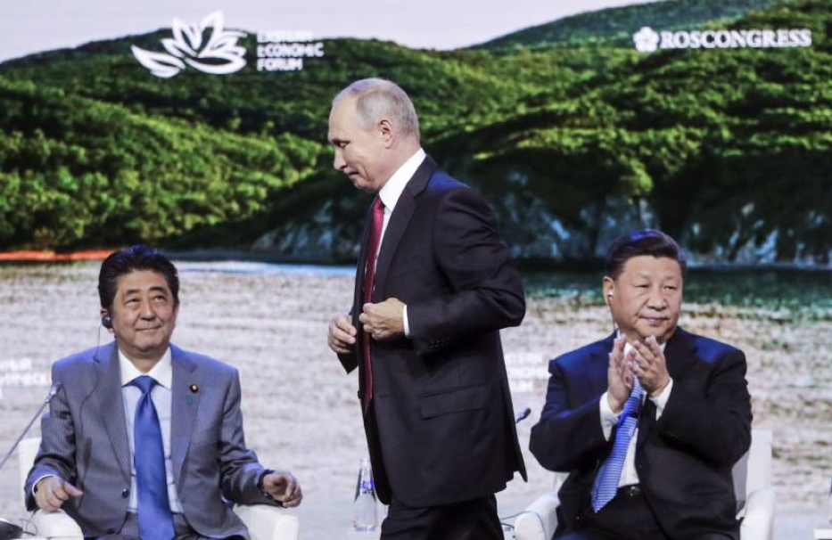[Russian President Vladimir Putin (center) walks back to his on-stage seat after delivering a speech as Japanese Prime Minister Shinzo Abe (left) and Chinese President Xi Jinping (right) look on at a Sept. 12, 2018, plenary session of the Eastern Economic Forum, held in Vladivostok, Russia. Credit:  Mikhail Metzel/TASS Host Photo Agency/Pool via Reuters ]