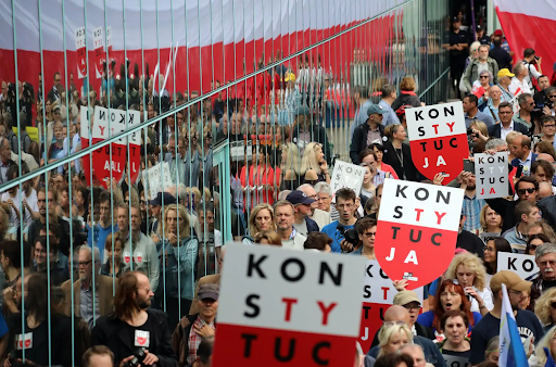 """Protesters carrying signs reading """"CONSTITUTION"""" rally in front of the Supreme Court building in Warsaw against the judicial reform that was signed into law in early July 2018. Photo:  Agencja Gazeta/Reuters"""