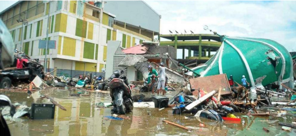 Local residents surveying the extent of the damage done by the tsunami in Palu, Central Sulawesi, Indonesia, Sunday, Sept. 30, 2018. (Source: Muhammad Rifki /  ABC News )