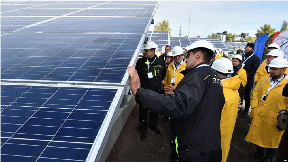 Visitors examine solar panels during open ceremony of the solar power plant next to the Chernobyl nuclear plant in Ukraine. Photo: Genya Savilov/ Agence France-Presse