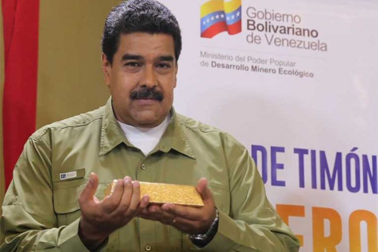 """Photo: """"Venezuelan President Nicolás Maduro hefts a bar of gold purportedly dug and processed in the Arco Minero, though experts have their doubts.""""  Source:  Pulitzer Center"""