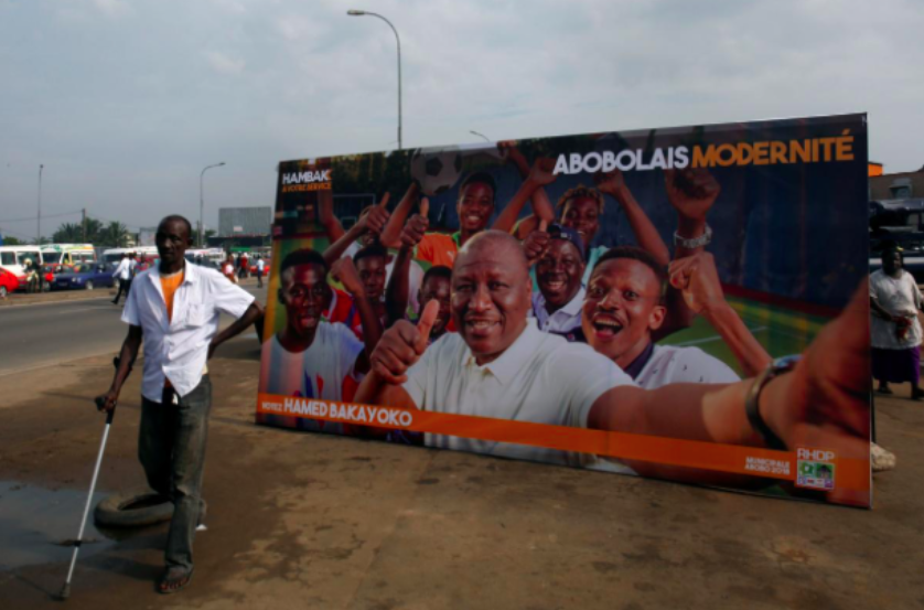 A man passes by a campaign poster of Hamed Bakayoko, a candidate running in the municipal election in Abidjan. Photo: Luc Gnago /  Reuters .