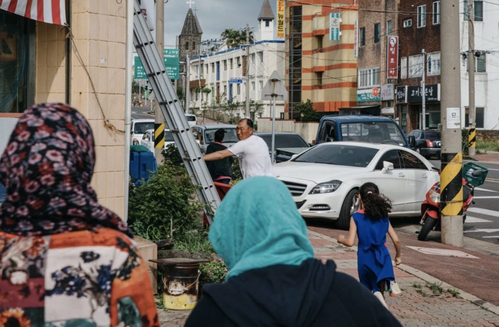 A Korean man turns his head towards two Yemeni refugee women on the streets of a town on Jeju Island. Credit:  Jun Michael Park/ The New York Times