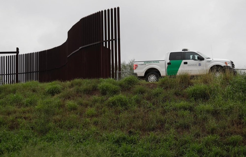 A US Customs and Border agent passes along the section of the wall in Hidalgo, Texas. Photo:  AP Photo/Eric Gay  .